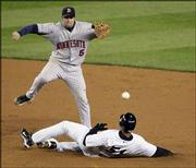 Minnesota second baseman Michael Cuddyer turns one of the Twins' five double plays as New York's Bernie Williams slides into second. The Twins set a record for most double plays in a nine-inning postseason game Tuesday in New York.
