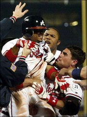 Atlanta's Rafael Furcal, left, is mobbed by teammates after hitting a game-winning home run. Andruw Jones is at center, and Marcus Giles is at right. Furcal's two-run shot in the 11th inning lifted the Braves past Houston, 4-2, Thursday in Atlanta.