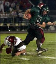 De Soto High quarterback Neil Erisman runs over Eudora's Luke Abel during the first half. Erisman had 22 carries for 194 yards and intercepted two passes on defense in the Wildcats' 12-7 victory Friday night in De Soto.