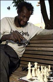 Willie Moore ponders his next move while playing chess at 10th and Massachusetts streets. The group of chess players has been ordered by the Lawrence Police to quit playing games on the ground, limiting the number of games the group can play at once.