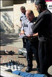 "Lawrence Police officers give Sherman ""Sly"" Talbert a warning about blocking the sidewalk with chess boards. Players now must confine their games to a bench at the corner of 10th and Massachusetts streets."