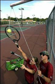 Lawrence High tennis coach Dick Wedel, right, helps junior Emily Thompson use a device Wedel invented to improve serve technique. During Wedel's 35 years of coaching, he has produced homemade, unorthodox teaching tools to help Lion tennis players improve.