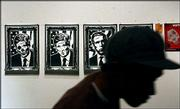 A visitor passes posters hanging on a wall during a political art exhibition at Track 16 Gallery in Santa Monica, Calif. The exhibition in this politically liberal beach city drew more than 350 people Friday night.