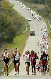Early leaders in a 4K run climb a steep hill on an entrance road to Clinton State Park.