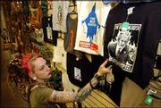 Kristen Ferrell, body jewelry manager at Third Planet, 2 E. Ninth St., straightens an anti-Bush T-shirt. The store sells anti-Bush materials on everything from playing cards to posters to T-shirts. Ferrell arranged the display Thursday.