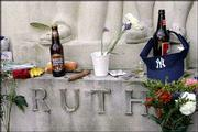 "A Kosher hot dog, cigar, Boston beer, coins, flowers and other items are left by New York Yankees fans at the grave of ""Babe"" Ruth in the Cemetery of the Gate of Heaven in Hawthorne, N.Y. Yankees fans made the offerings Monday in hopes the so-called ""Curse of the Bambino"" again afflicts the Red Sox in the American League championship series, which starts today in New York"