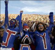 KU students Jesse Plous, left, Lindsey Gold, center, and Josh Bailey cheer before the start of the Jayhawks' game against Kansas State. A near-sellout crowd watched the Jayhawks beat the Wildcats, 31-28.