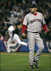 Boston pitcher Curt Schilling watches the flight of a New York Yankee base hit during Game 1 of the ALCS. The Yankees won, 10-7, Tuesday in New York.