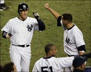 New York's Hideki Matsui, left, accepts congratulations from teammates Alex Rodriguez, right, and Bernie Williams after scoring a run. Matsui drove in five runs in the Yankees' 10-7 victory over Boston on Tuesday night in New York.