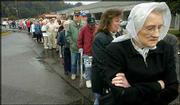 Miriam Majors, 82, clutches herself to keep warm in a light drizzle while waiting in line for a flu shot in Roanoke, Va. More than 400 people over the age of 65 stood in line Tuesday, starting before dawn, to receive their shots. The United States is trying to find additional supplies of flu vaccine anywhere it can.