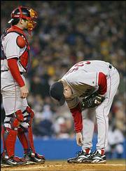 Boston starter Curt Schilling examines his right foot in the fourth inning with catcher Jason Varitek. Schilling and the Red Sox won, 4-2, Tuesday night in New York.