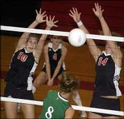 Lawrence High's Elise McDonald, left, and Bonnie Toplikar block a spike. The Lions swept their home quad Tuesday at LHS.