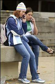 Kansas University students Lisa Bartell, left, a Salina freshman, and Kelly Spencer, Overland Park freshman, chat on their cell phones between classes Wednesday in front of Wescoe Hall. People who use only cell phones and don't have land lines often are missed by pollsters during election season, meaning a large number of voters -- mostly young people -- aren't included.