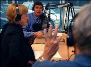 Radio host Jim Cates, right, signals to Rep. Jim Ryun how many seconds he has left to answer a listener's question during a debate Tuesday with opponent Nancy Boyda on the AM-1440 KMAJ Jim Cates Show in Topeka. Ryun and Boyda also are scheduled to debate today at KTWU, Topeka's public television station.
