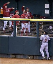 Players in the St. Louis bullpen celebrate while Houston right fielder Jason Lane watches a two-run home run by Jim Edmonds land in the stands. Edmonds' 12th-inning homer gave the Cardinals a 6-4 victory in the sixth game of the NL championship series Wednesday in St. Louis.