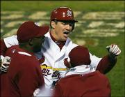 St. Louis' Scott Rolen, center, celebrates after hitting a two-run homer. The Cards won, 5-2, Thursday night in St. Louis.