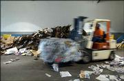 To capture a sense of motion in this image, the photographer used a slow shutter speed and focused on a stationary subject, in this case the pile of cardboard in the background. By exposing the photograph as the forklift driver passed through the frame, the moving foreground subject was blurred, signifying motion.