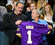President Bush is presented a Minnesota Vikings jersey by Vikings head coach Mike Tice, left, who introduced him at a campaign rally Saturday in Minneapolis.