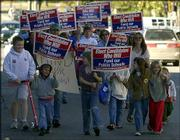 Marchers make their way up Seventh Street during a rally for public education funding. Saturday's rally began at Buford M. Watson Jr. Park, Seventh and Kentucky streets, and ended at the Douglas County Courthouse, 1100 Mass.