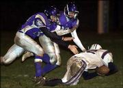 Baldwin defenders Ricky Baker, left, and Austin Inzer, center, tackle Louisburg's Chad Roberts in the first half.