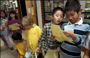 Hillcrest third-grader Yang Tang Li, second from right, looks at who his classmate Rob Aga voted for on his Kids Voting ballot. The students chose their favorite candidates on Tuesday.