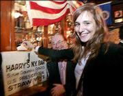 Emilie Marsh from New York casts her fake ballot in a U.S. presidential election straw vote at Harry's Bar in Paris. Democrat candidate John Kerry won the straw poll with 419 votes against 242 for President George W. Bush.