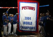 The Detroit Pistons celebrate their 2004 NBA title as their championship banner is raised. The Pistons defeated Houston, 87-79, Tuesday night in Auburn Hills, Mich.
