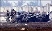 American soldiers pass a vehicle damaged in a car bomb explosion at a checkpoint at the entrance of the Baghdad International Airport. Wednesday's bombing killed an American soldier and wounded another.