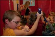 Tyler Archinal, a second-grader, looks for signs of his muscles while participating in a program at Perry Elementary School. Students participated Thursday in Body Walk, a 35-foot by 40-foot enclosed walk-through exhibit representing the human body.