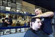 Rex Porter cuts the hair of customer Keiv Spare, a Kansas University senior from Parsons, at Rex's Stadium Barber Shop, 1033 Mass. Rex bought the longtime RC's Stadium Barber Shop after being a barber at Downtown Barber Shop for 17 years. Porter said Friday that he originally wanted to remodel the wall featuring pictures of local athletes, but since had decided leave it alone.