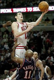 Chicago's Kirk Hinrich, top heads to the basket as New Jersey's Jacque Vaughn draws a foul in a battle of former Kansas University standouts. Hinrich scored a career-high 34 points, but the Bulls lost to New Jersey, 111-106 in double overtime, Friday night in Chicago.