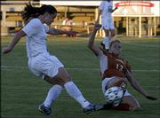 Kansas University sophomore defender Holly Gault, left, boots the ball past Texas defender Paige Carmichael in the first half. The Jayhawks lost, 3-2 in double overtime, in the semifinals of the Big 12 Conference soccer tournament Friday in San Antonio.