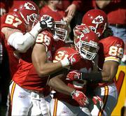 Chiefs running back Priest holmes (31) accepts congratulations from teammates Chris Bober (67), Tony Gonzalez (88) and Jason Dunn (89) after scoring a touchdown against Atlanta. Holmes scored four times in the Oct. 24 game in Kansas City, Mo.