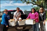 University National Bank employees, from left, Lori Kloepper and Annette Thede deliver nonperishable foods to Pelathe Community Resource Center during the Fall Day of Caring. Caroline Hicks, of Pelathe center, and Linda Elwell, right, chairwoman of the Fall Day of Caring, helped unload the food Sept. 24 at the center.
