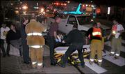 A victim of an early-evening accident at Ninth and Massachusetts streets is loaded onto a gurney by an ambulance crew. Saturday's accident involved a police chase that ended when the pursued vehicle crashed into another car, which then hit another car. Three people were taken to the hospital.