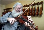 Steve Mason, a multi-instrumentalist, member of the Alferd Packer Memorial String Band and long-time supporter of musical arts in Lawrence, is the recipient of this year's Phoenix Award for Music Arts. In keeping with his zany sense of humor, Mason has a friend lend him a third hand while fiddling a tune.