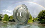 """Mobility,"" a sculpture by Lawrence artist Shellie Bender, was fabricated by A. Zahner Co. of Kansas City, Mo. The sculpture is framed by a rainbow following an August thunderstorm."