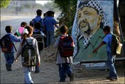 Palestinian schoolchildren pass by a painting of Palestinian leader Yasser Arafat as they walk in the main road between Rafah and Khan Younis, southern Gaza Strip. Palestinian Prime Minister Ahmed Qureia travelled to the Gaza Strip on Saturday for talks with rival Palestinian groups aimed at preserving calm during Yasser Arafat's absence, Qureia's office said.