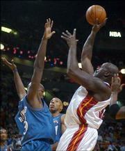 Miami's Shaquille O'neal, right, shoots over Washington's Brendan Haywood, left, as Michael Ruffin, center, watches. O'Neal had 20 points and nine rebounds, and the Heat beat the Wizards, 103-93, Tuesday night in Miami.