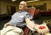 Chuck McPheeters squeezes his hand to get the blood flowing in his arm while giving blood at the American Red Cross blood drive at First Christian Church, 1000 Ky. McPheeters, also a Red Cross volunteer, has given more than 100 pints of blood, including the one he donated Wednesday.