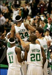 Boston's Paul Pierce is lifted by teammates, from left, Walter McCarty, Marcus Banks, Gary Payton and Raef LaFrentz after hitting the game-winning shot at the buzzer. The Celtics defeated the Trail Blazers, 90-88, Wednesday night in Boston.