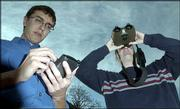 Kansas University researchers Matt Dunbar, left, and John Kostelnick, demonstrate how a Global Positioning device, a personal data assistant and binoculars are used as part of a new land-mine detection procedure.