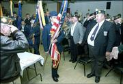 Don Dalquest, American Legion Post 14 commander, far right, salutes as Kansas University ROTC cadets bring in the colors for a Veterans Day ceremony at the VFW, 138 Ala.
