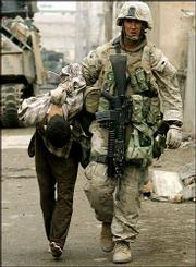 A U.S. Marine leads away a captured Iraqi man in Fallujah, Iraq. Trooping past dead bodies and abandoned weapons, U.S. Marines fighting their way through Iraq's rebel-infested Fallujah are seeking fighters and guns in the battle against Sunni Muslim insurgents.