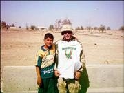 Darrell Hunsaker shows off a little bit of home -- a Free State High School shirt -- while serving in the U.S. Army at Camp Victory North in Baghdad, Iraq. He is pictured with Ali, whose parents were killed by Saddam Hussein's police.