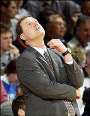 """Kansas University coach Bill Self checks the scoreboard during the Jayhawks&squot; 79-70 victory over Washburn. The Jayhawks went 2-0 in the exhibition season, but Self hopes Sunday&squot;s narrow win in Allen Fieldhouse will serve as a """"wake-up call"""" for the Jayhawks."""