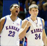 Kansas' Wayne Simien, left, yells after teammate Christian Moody scored and drew a foul in the Jayhawks' narrow exhibition victory over Washburn.