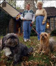 Jim and Ruthie Amen show their dogs Dolly, left, and Toto on Thursday outside their Leawood, Kan., home. The retired couple operate Angel Watchers Pet Sitting Service as a way to keep active.