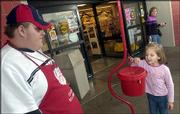 Salvation Army bell ringer Mike McKeehan, Lawrence, thanks Megan Towle, 6, Lawrence, as she drops some coins in the kettle outside the Dillons store at 1015 W. 23rd St. The annual fund drive opened Saturday.