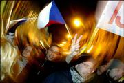 A marcher flashes V-sign and waves a Czech flag during an event commemorating the 15th anniversary of the 1989 Velvet Revolution in Prague, Czech Republic. Rock music and stirring speeches echoed Wednesday through the streets of Prague.